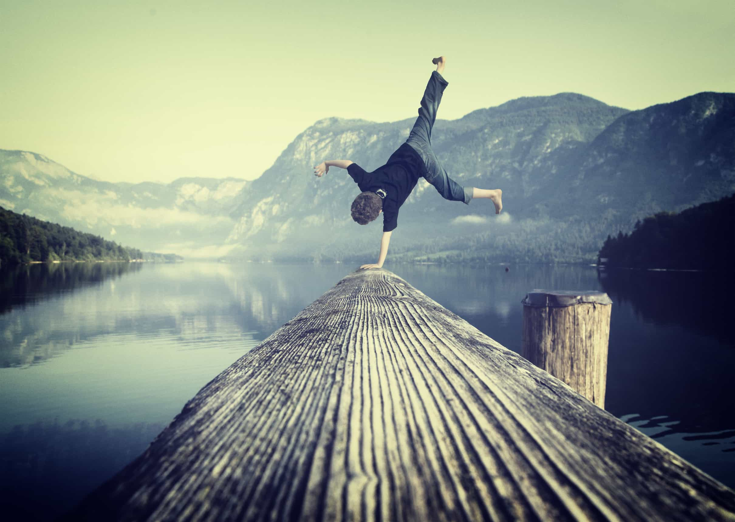 Young boy handstanding on jetty - Youth and vitality